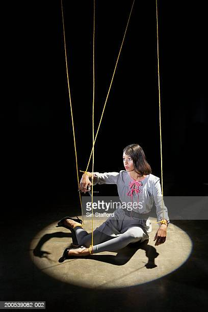 Woman tied in strings sitting on floor with spotlight