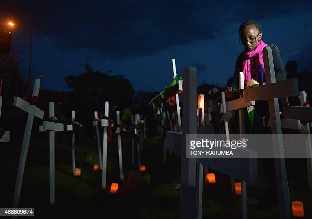 A woman ties a scarf in the likeness of Kenya's national standard on a wooden cross at FreedomCorner in Uhuru Park in Nairobi on April 7 2015 during...