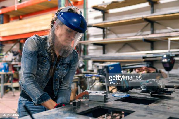 woman tightening a vice to secure metal in place - helmet visor stock pictures, royalty-free photos & images