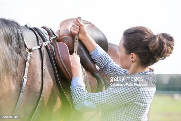 Woman tightening horse saddle for horseback riding