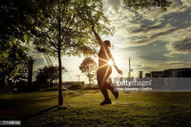 woman tightrope walking at park during sunset - oslo stock photos and pictures