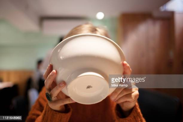 Woman tipping a bowl to her face drinking the remainder of her ramen broth soup in a restaurant in London United Kingdom