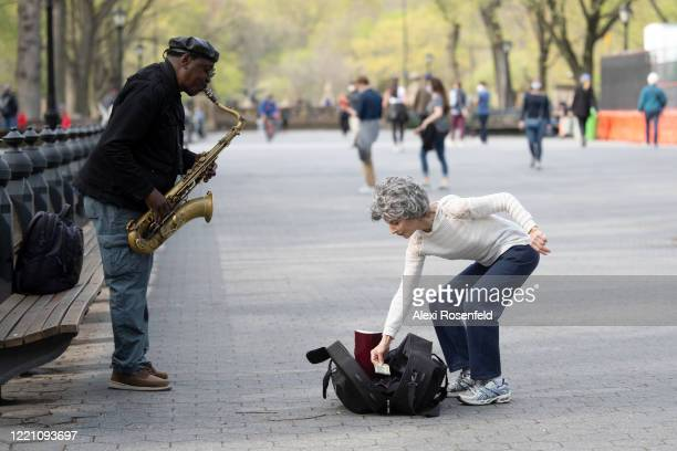 A woman tips a saxophone player in Central Park as temperatures rose amid the coronavirus pandemic on April 25 2020 in New York City United States...