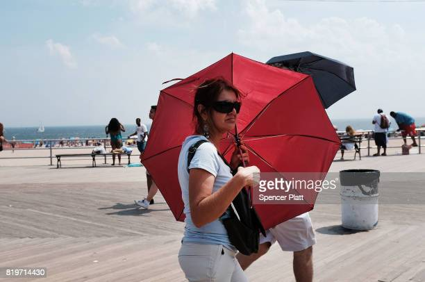 A woman tires to stay out of the sun on the boardwalk at Coney Island on July 20 2017 in the Brooklyn borough of New York City Throughout the region...