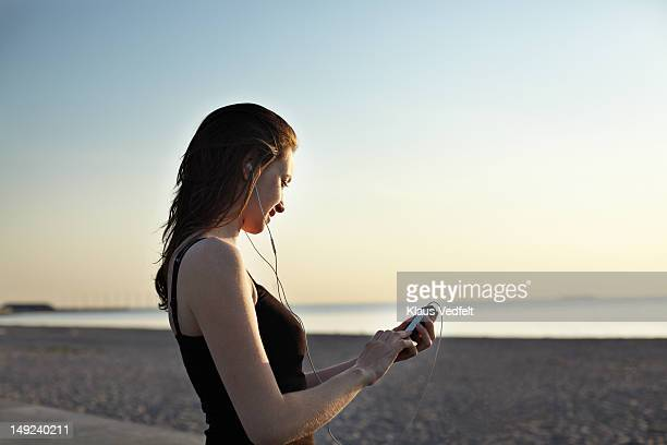 Woman tjecking her phone at the beach