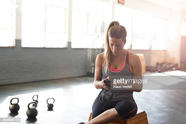 woman tjecking results on smartphone at gym - checking sports stock pictures, royalty-free photos & images