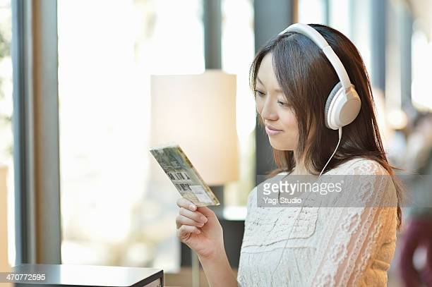 Woman to listen to the music CD in record shop