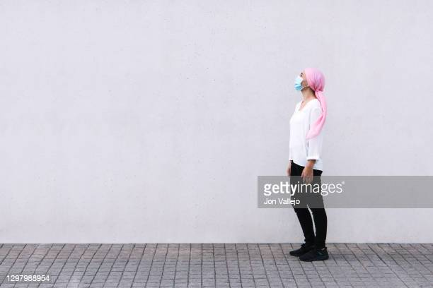 woman to the right of the image and looking up with a pink scarf in reference to cancer and with a mask, black pants and white blouse. - fist stock pictures, royalty-free photos & images