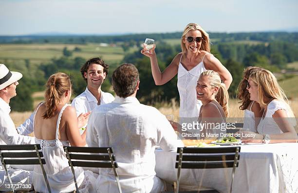 woman toasting at table outdoors - 40 49 jaar stockfoto's en -beelden