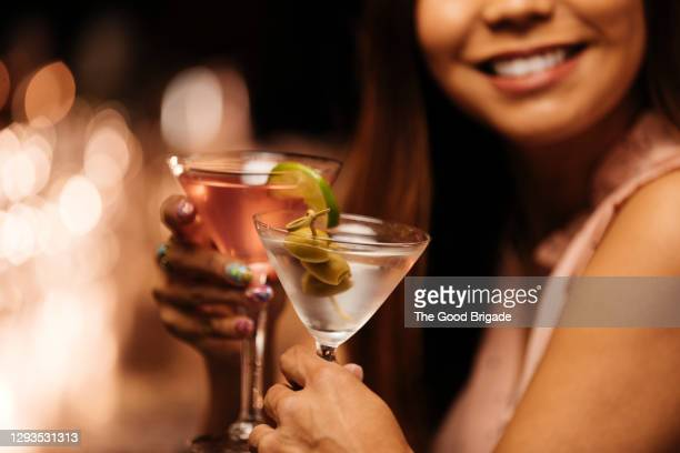 woman toasting glasses with date at bar - refreshment stock pictures, royalty-free photos & images