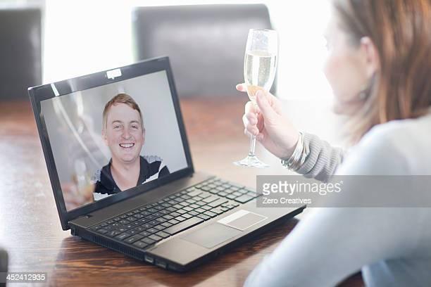 Woman toasting husband using video call