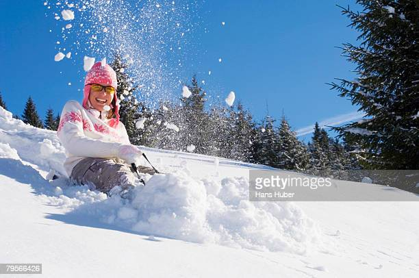 Woman tobogganing in mountains