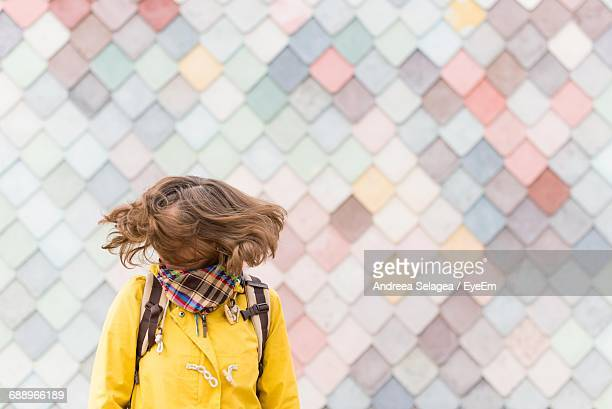 Woman Tossing Hair Against Patterned Wall