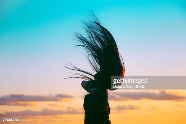 Woman Tossing Hair Against Sky During Sunset