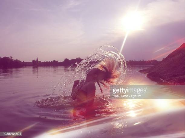 woman tossing hair in lake against sky - straubing stock pictures, royalty-free photos & images