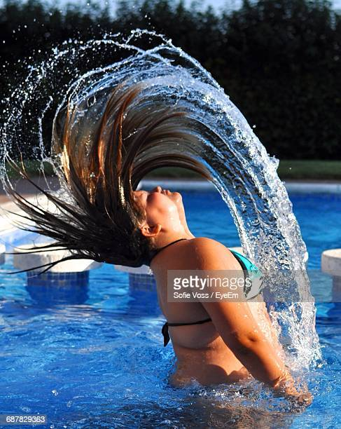 Woman Tossing Her Wet Hair In Swimming Pool