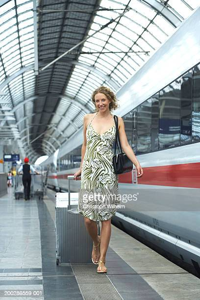 woman toting luggage on train station platform - one mid adult woman only stock pictures, royalty-free photos & images