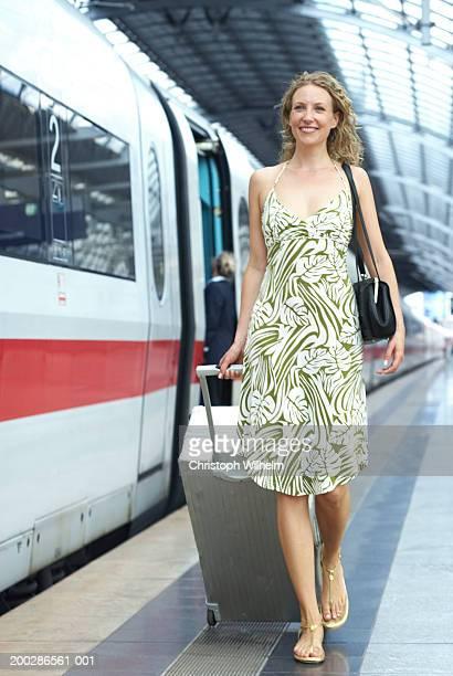Woman toting luggage on train station platform