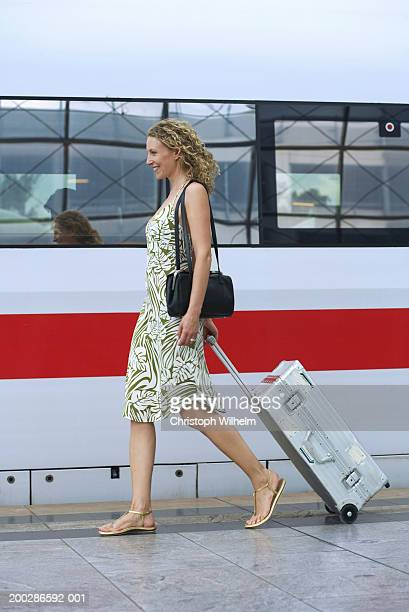Woman toting luggage on train station platform, side view