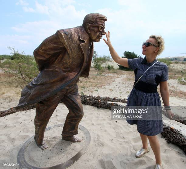 A woman touches a bronze statue made by sculptor Klaudijus Pudymas and dedicated to French playwright philosopher novelist and political activist...
