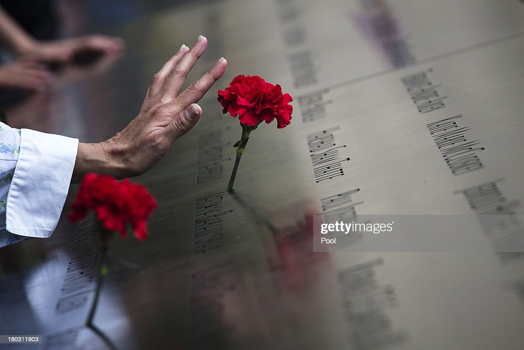 A woman touches a carnation left on a name inscribed into the North Pool during 9/11 Memorial ceremonies marking the 12th anniversary of the 9/11 attacks on the World Trade Center in New York on September 11, 2013 in New York City. The nation is commemorating the anniversary of the 2001 attacks which resulted in the deaths of nearly 3,000 people after two hijacked planes crashed into the World Trade Center, one into the Pentagon in Arlington, Virginia and one crash landed in Shanksville, Pennsylvania. Following the attacks in New York, the former location of the Twin Towers has been turned into the National September 11 Memorial & Museum.