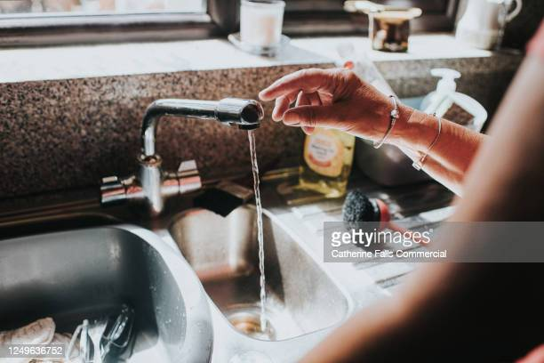 woman touches a chrome tap in a kitchen - human limb stock pictures, royalty-free photos & images