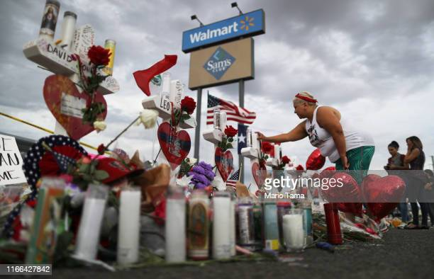 A woman touches a cross at a makeshift memorial for victims outside Walmart near the scene of a mass shooting which left at least 22 people dead on...