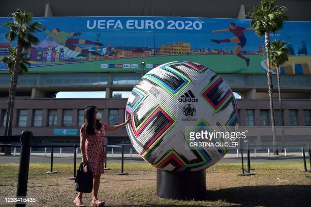 Woman touches a giant ball in front the La Cartuja stadium in Seville on June 12, 2021. - La Cartuja stadium will host UEFA EURO 2020 Group E...