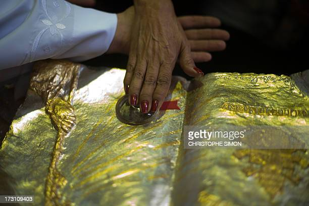 A woman touches a relic after a mass officiated by Cardinal Stanislaw Rylko to celebrate the arrival in Brazil of the relics of blessed John Paul II...