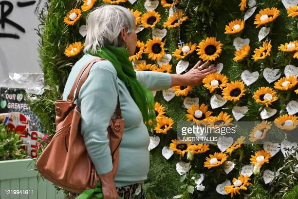 A woman touches a wall of remembrance as she pays her respects beside Grenfell tower in west London on June 14 on the third anniversary of the...