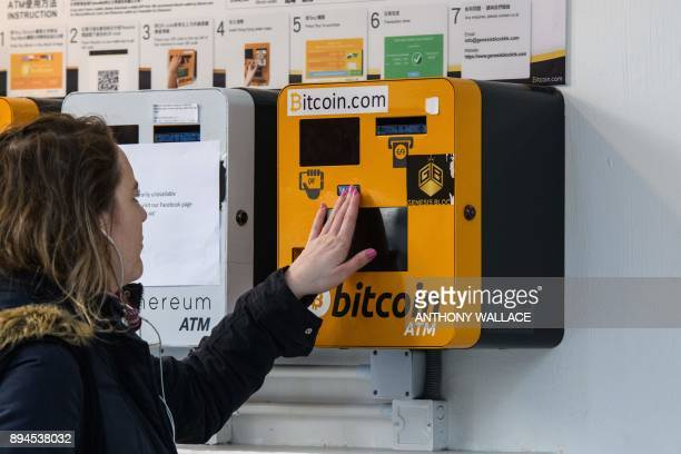 A woman touches an ATM machine for digital currency Bitcoin in Hong Kong on December 18 2017 Bitcoin has soared in recent weeks breaking numerous...