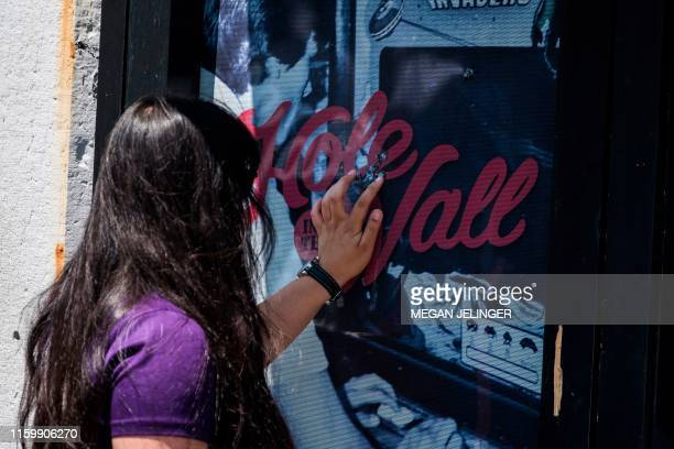 A woman touches bullet holes at Hole in the Wall bar after the mass shooting over the weekend in Dayton Ohio on August 5 2019 US President Donald...