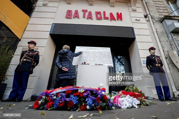Woman touches the commemorative plaque at the entrance of the Bataclan in Paris on November 13 during a ceremony held for the victims of the Paris...