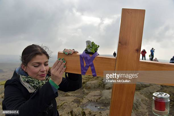 Woman touches the cross situated where St. Patrick used to sit on a rock tending sheep as hundreds of people make the St. Patrick's Day pilgrimage to...