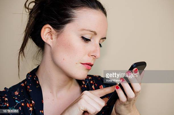 woman touches the screen of cell phone. red nails - red nail polish stock pictures, royalty-free photos & images