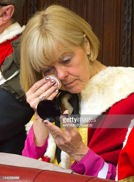 A woman touches up her makeup as she waits to hear Britain's Queen Elizabeth II read the Queen's Speech in the Chamber of the House of Lords in the...
