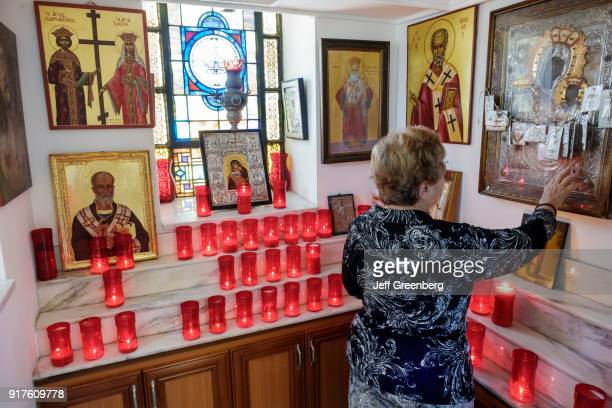 A woman touching an icon inside the St Nicholas Greek Orthodox Cathedral