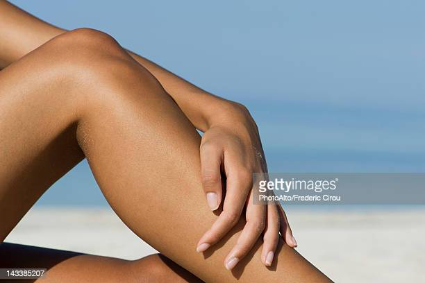 Woman touching bare legs at the beach, cropped
