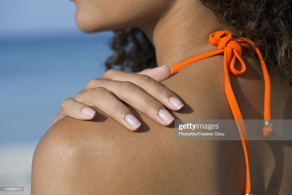 Woman touching bare shoulder at the beach, cropped : Stock Photo
