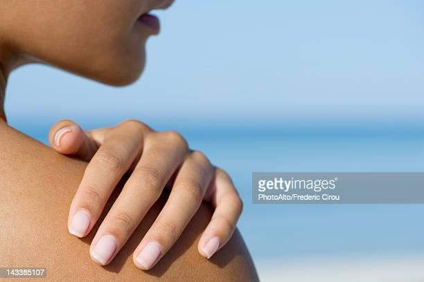woman touching bare shoulder, cropped - schouder stockfoto's en -beelden