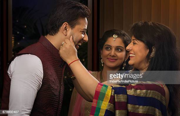 Woman touching cheeks of his son-in-law and smiling
