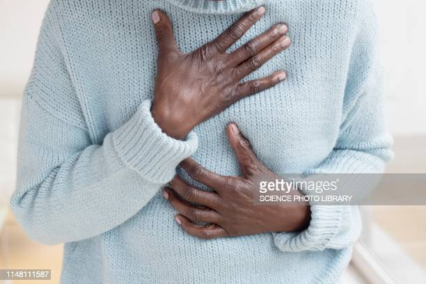 woman touching chest in pain - chest torso stock pictures, royalty-free photos & images