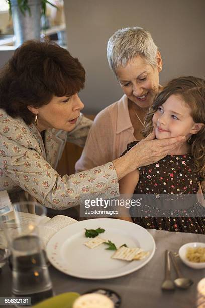 Woman touching child in affectionate way during sedar ritual