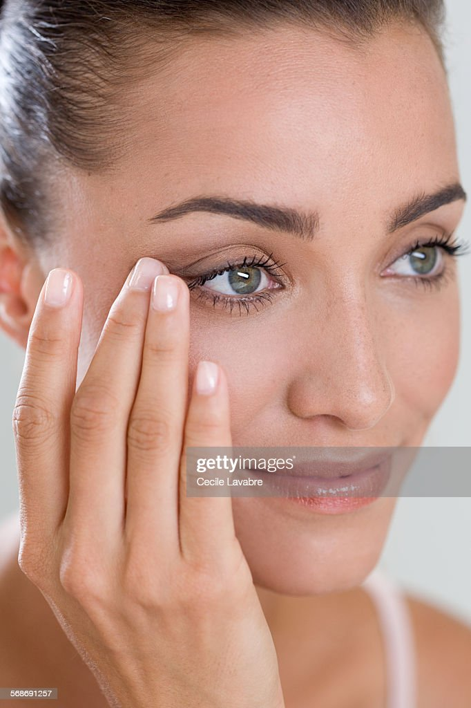 Woman touching eye wrinkles with finger : Stock Photo