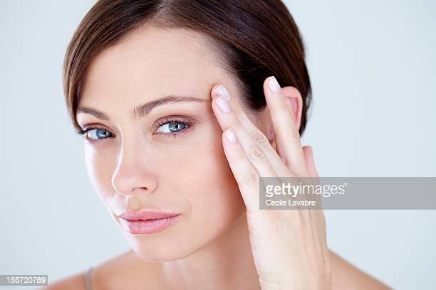 woman touching eye wrinkles with her finger - forehead stock pictures, royalty-free photos & images