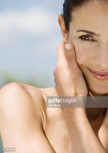 Woman touching face and smiling