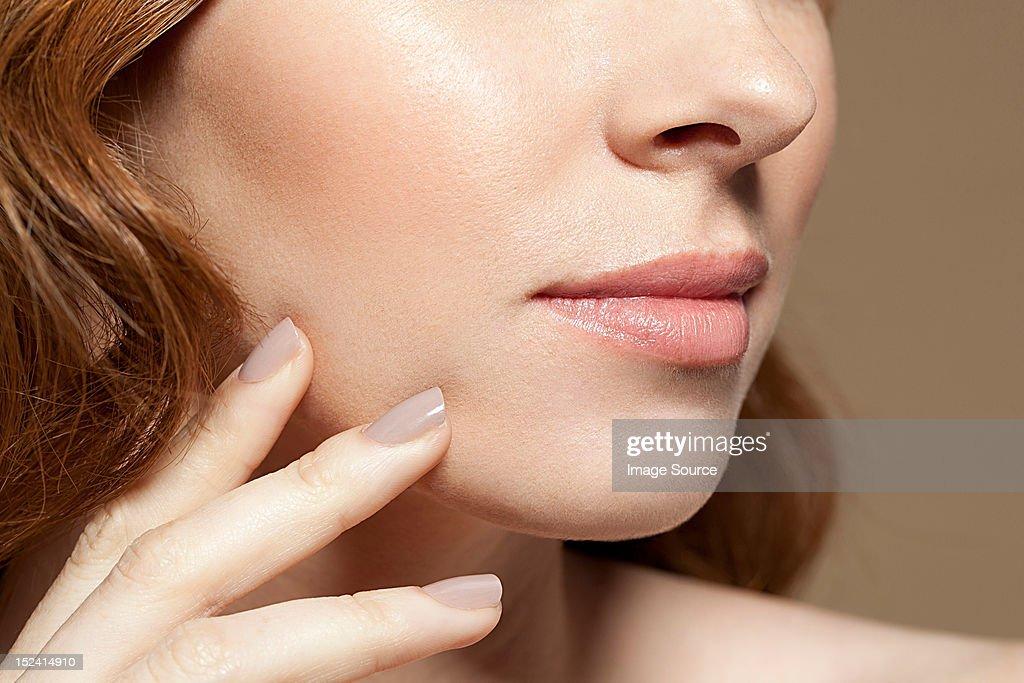 Woman touching face, close up : Stock Photo