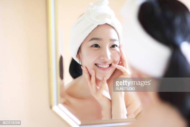 woman touching face in mirror - korean ethnicity stock pictures, royalty-free photos & images