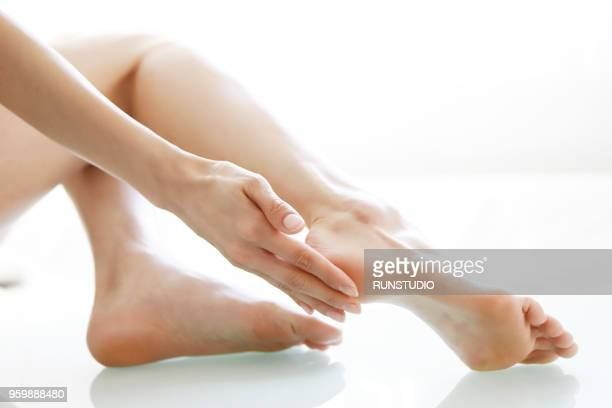woman touching feet, low section, close-up - japanese women feet stock photos and pictures