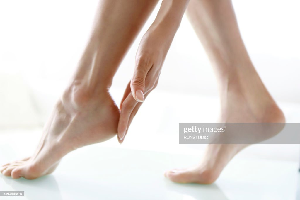Woman touching feet, low section, close-up : Stock Photo